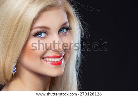Portrait of a beautiful blonde woman on black background .