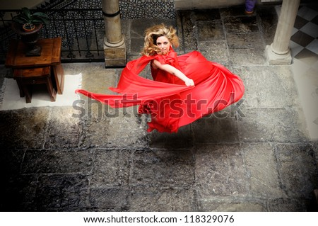Portrait of a beautiful blonde woman, wearing a red dress, jumping - stock photo