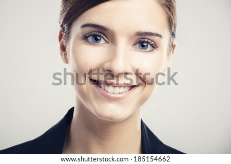Portrait of a beautiful blonde woman with blue eyes smiling - stock photo