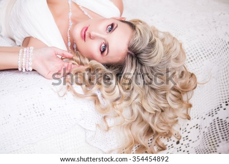 Portrait of a beautiful blonde woman with curly long hair lying on the bed