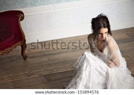 Portrait of a beautiful bride sitting on the floor and holding herself - stock photo