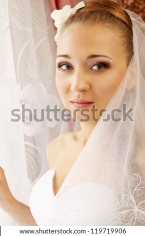 Portrait of a beautiful bride standing at the window - stock photo