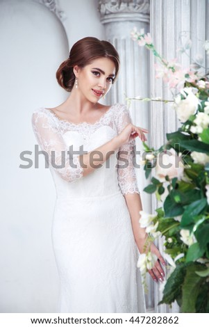 Portrait of a beautiful brunette bride in an elegant hall with columns