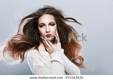 Portrait of a beautiful brunette girl with fluttering fly hair with wind. Windy hair