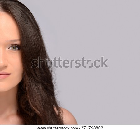 Portrait of a beautiful brunette girl with green eyes and perfect lips wearing makeup and smiling. Attractive young happy woman with long hair. Half face beauty woman - stock photo