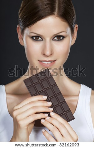 Portrait of a beautiful brunette holding a chocolate bar in both hands