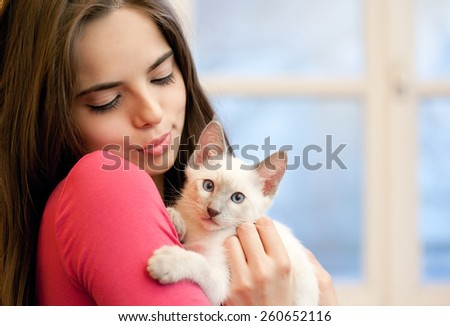 Portrait of a beautiful brunette holding a cute kitten. - stock photo