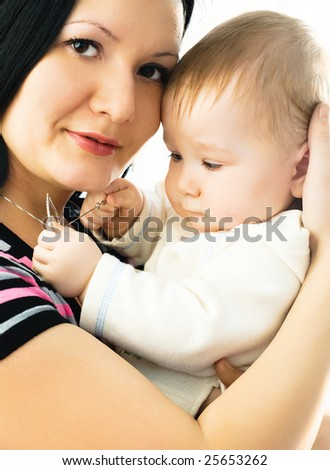 portrait of a beautiful brunette mother with her ten months old baby - stock photo