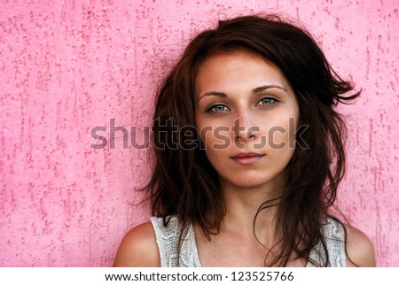 Portrait of a beautiful brunette on pink background - stock photo