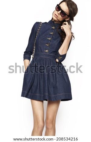 Portrait of a beautiful brunette posing in sunglasses in the studio - stock photo