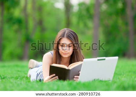 portrait of a beautiful brunette student girl with laptop computer and book on the green grass in the park in spring time.