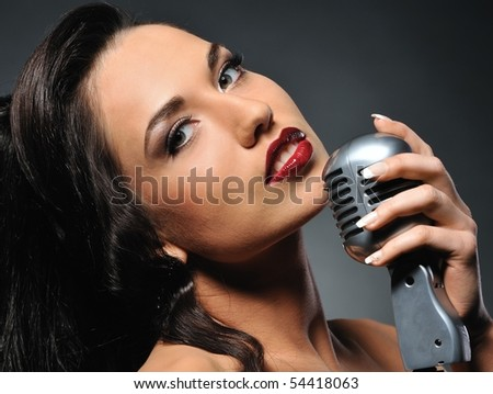 Portrait of a beautiful brunette with a retro microphone - stock photo