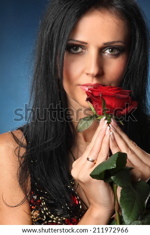 Portrait of a beautiful brunette with a rose in his hands. long hair. beautiful eyes. sexy lips. - stock photo