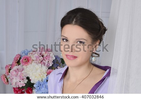portrait of a beautiful brunette with flowers in the background