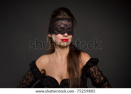 Portrait of a beautiful brunette with lacy blindfolded, closeup - stock photo