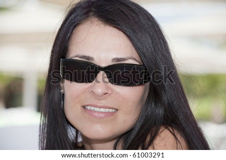portrait of a beautiful brunette with sunglasses - stock photo
