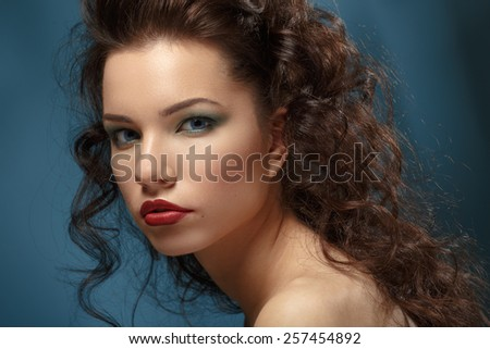 Portrait of a beautiful brunette with wavy hair and bright makeup on blue background - stock photo