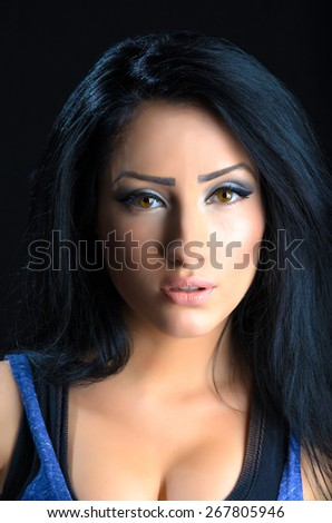 Portrait of a beautiful brunette woman against a black background - stock photo