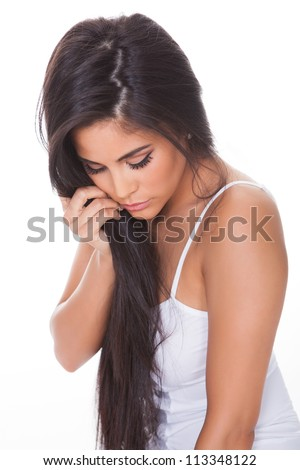 Portrait of a beautiful brunette woman in profile with downcast eyes and a serious expression isolated on white