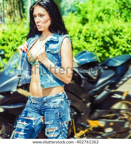 Portrait of a beautiful brunette woman stand near black sports motorcycle Very hot sexy young femme girl opens denim vest, show big tits against green summer bush background - stock photo