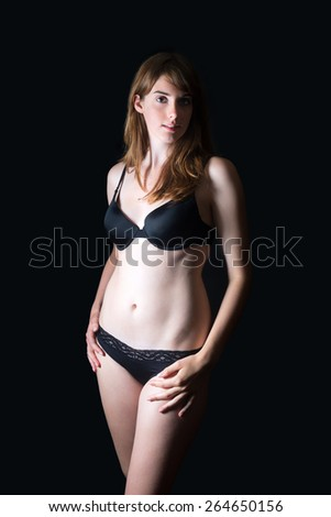 Portrait of a beautiful brunette woman wearing black underwear in front of black studio background - stock photo