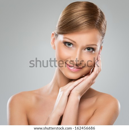 Portrait of a beautiful brunette woman with brown hair and naked shoulders posing over a grey background - stock photo