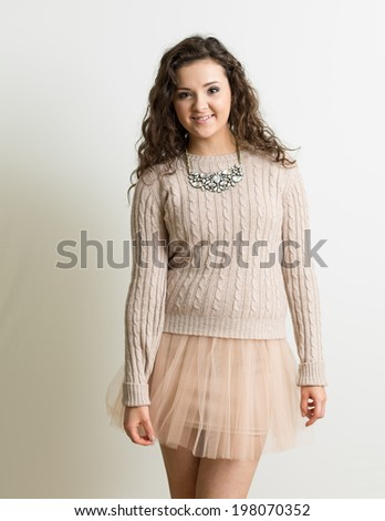 Portrait of a beautiful brunette woman with curly hair wearing a tutu like pink mini skirt against a white background. Also wearing a necklace - stock photo