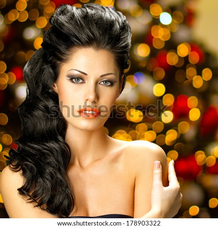 Portrait of a beautiful brunette woman with long hair.  Fashion model posing at studio. - stock photo