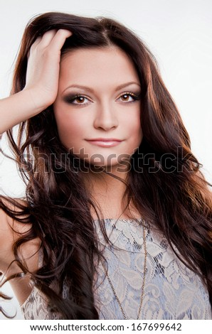 Portrait of a beautiful brunette woman with long hair on a light background