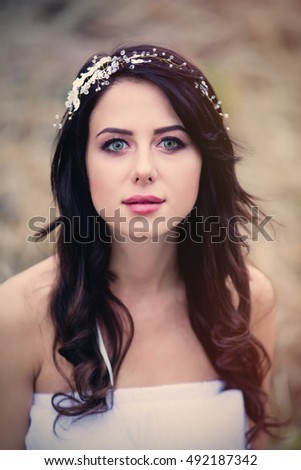 Portrait of a beautiful brunette woman with wreath in autumn outdoor