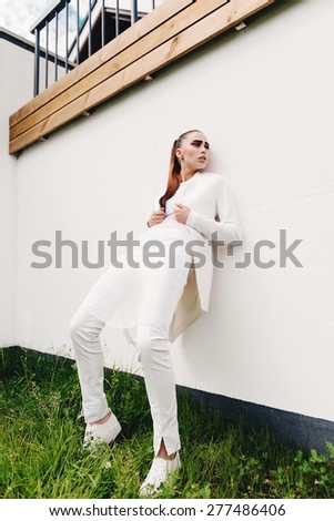 Portrait of a beautiful brunette young girl in a white, outdoor  - stock photo