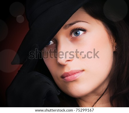 Portrait of a beautiful brunette young woman with black hat and gloves - stock photo