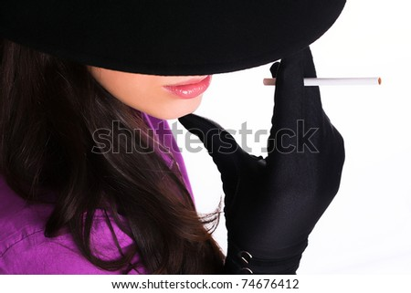 Portrait of a beautiful brunette  young woman with black hat,gloves and cigar - stock photo
