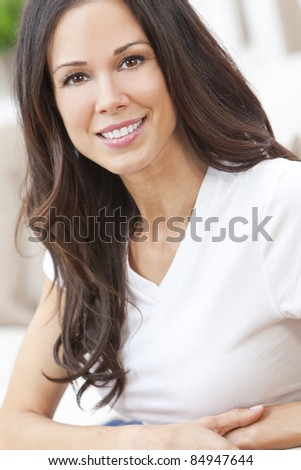 Portrait of a beautiful brunette young woman with perfect teeth smiling and relaxed - stock photo
