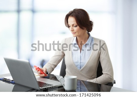 Portrait of a beautiful business woman sitting in the office - stock photo