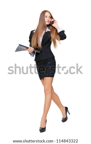 Portrait of a beautiful business woman talking on the cell phone and holding a folder while walking on white background - stock photo