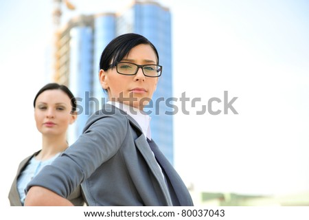Portrait of a beautiful business woman with a female colleague in the background against constructing office building. Picture taken from below - stock photo