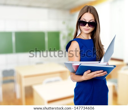 Portrait of a beautiful business woman with folders and dark glasses - stock photo