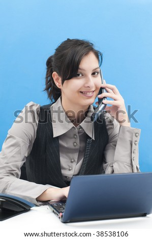 Portrait of a beautiful business woman working at her desk with a laptop, speaking at the office phone