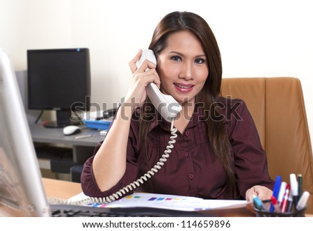 Portrait of a beautiful business woman working on her desk in an office environment - stock photo