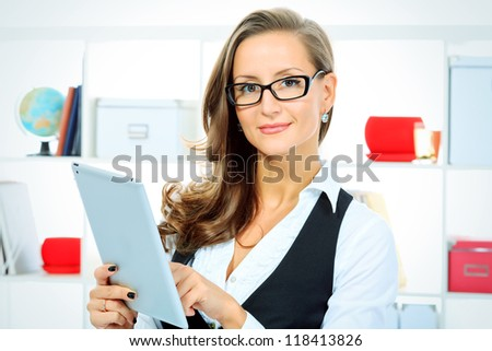 Portrait of a beautiful business woman working with touchpad pc at the office.