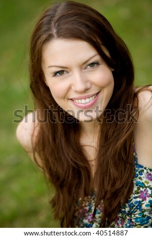 Portrait of a beautiful casual woman smiling outdoors - stock photo