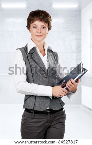Portrait of a beautiful caucasian businesswoman with books - stock photo