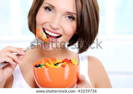 Portrait of a beautiful caucasian smiling young woman eats vegetable salad