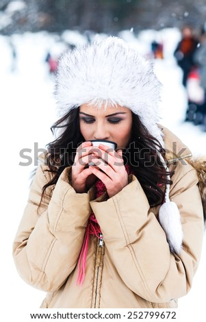portrait of a beautiful, cheerful girl in winter,drinking tea, coffee - stock photo