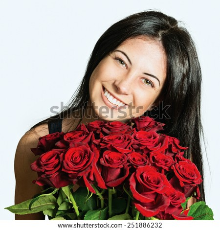 Portrait of a beautiful cheerful girl with a bouquet of roses - stock photo