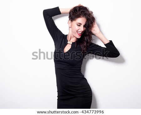 Portrait of a beautiful cheerful sensuality woman in black dress posing over white background - stock photo