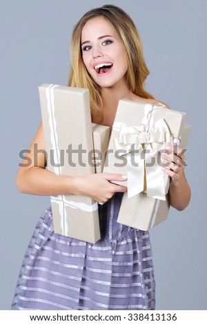 Portrait of a beautiful cheerful woman in gala dress holding present boxes - stock photo