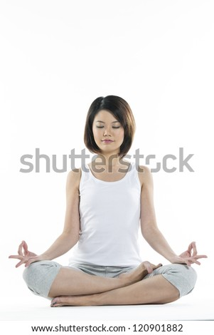 Portrait of a beautiful Chinese woman in Lotus yoga position with eyes closed. - stock photo