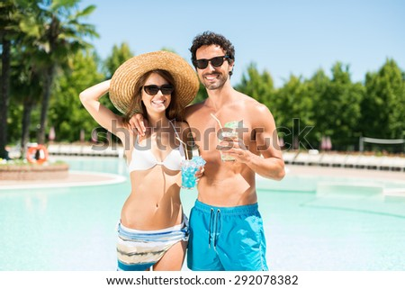 Portrait of a beautiful couple enjoying the sun in front of a pool - stock photo